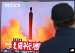 "FILE - A man watches a TV news program, Oct. 16, 2016, showing a file image of a missile launch conducted by North Korea. The letters read ""North attempted to fire a midrange Musudan missile in June."""