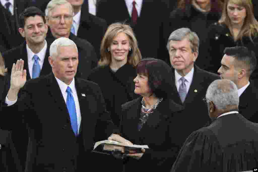 Wakil Presiden Mike Pence diambil sumpahnya oleh Hakim Agung Clarence Thomas sementara istrinya Karen memegang alkitab saat inaugurasi ke-58 di Gedung Capitol di Washington, 20 Januari 2017.