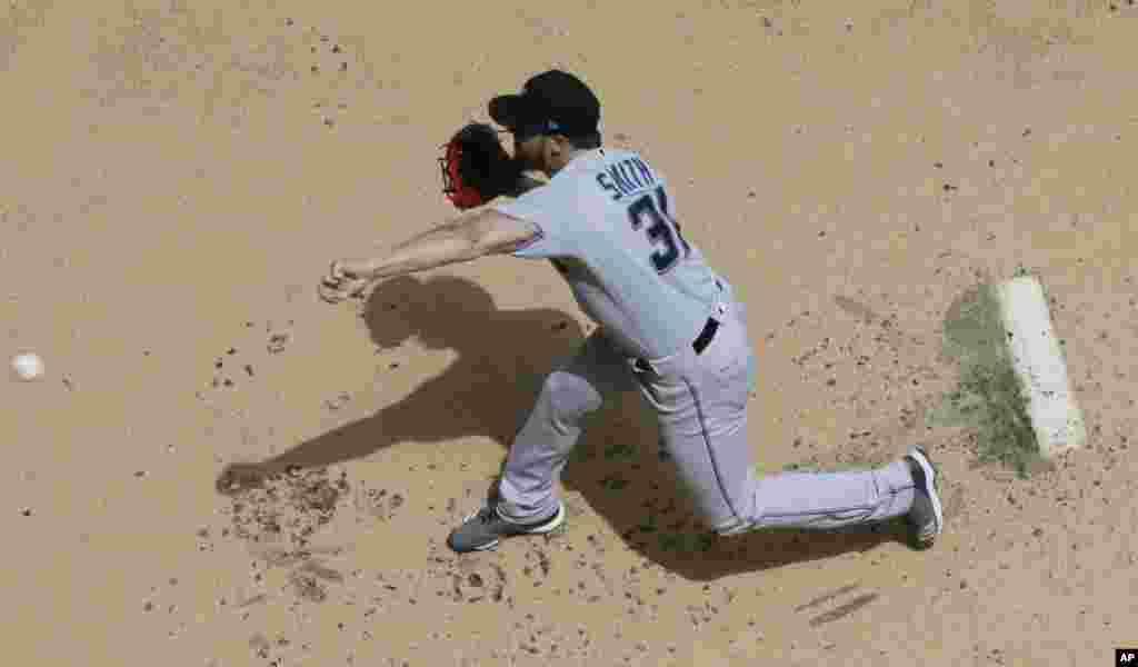 مسابقات بیسبال در آمریکا به مراحل نهایی خود رسیده است. بازیکن تیم میامی مقابل میلواکی، سعی در دریافت توپ دارد.