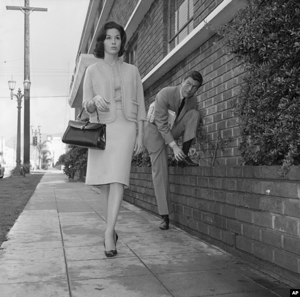 Actor Dick Van Dyke, right, looks on as actress Mary Tyler Moore walks by, Feb. 22, 1962, Los Angeles, California.