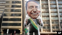 Supporters of Jair Bolsonaro, presidential candidate for the National Social Liberal Party who was stabbed during a campaign event days ago, exhibit a large, inflatable doll in his image in Sao Paulo, Brazil, Sept. 9, 2018.
