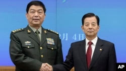 Chinese Defense Minister Chang Wanquan, left, poses with his South Korean counterpart, Han Min-goo, for photographers prior to a meeting at the Defense Ministry in Seoul, Feb. 4, 2015.