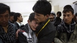 A Pakistani man comforts another mourning for a family member who died in a bomb blast, at local hospital in Quetta, Pakistan on Feb. 16, 2013.