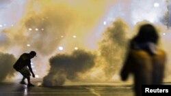 Cảnh sát dùng bom khói và hơi cay để thực thi lệnh giới nghiêm ở thị trấn Ferguson, bang Missouri.