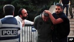 15 Temmuz darbe girişimi suçlamasıyla polis tarafından götürülen zanlıya tüküren bir kişi