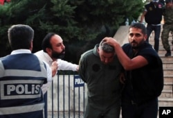 FILE - A civilian, second left, spits at a member of Turkey armed forces as he is escorted by police with a group of others for their suspected involvement in the attempted coup in Turkey, July 17, 2016.