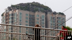 A man looks at a roof top villa with binoculars from an overhead bridge in Beijing, China, Aug. 13, 2013.