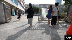 Cha mẹ đứng nhìn con em vào trường tiểu học tại Seoul ngày 25/8/2020.
