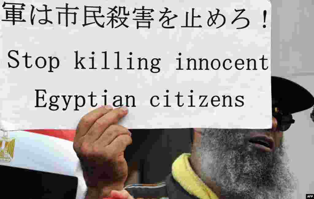 一名示威者8月18日在东京的埃及大使馆前集会时展示一个标语牌。