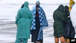 身穿防护服的俄罗斯医护人员在秋明附近的一个机场迎接俄罗斯军机从武汉撤回的侨民。(2020年2月5日)