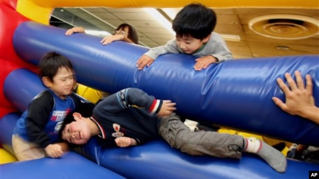 Children play in giant air cushions at the Fantasy Kids Resort in Ebina, west of Tokyo, March 2006.