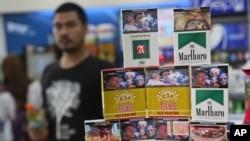 Bungkus-bungkus rokok yang memasang gambar peringatan, dipajang di sebuah toko di Jakarta (24/6). (AP/Tatan Syuflana)