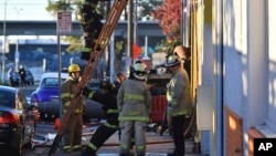 Firefighters assess the scene where a fire tore through a warehouse that had been converted into artists' studios early Dec. 3, 2016, in Oakland, California.