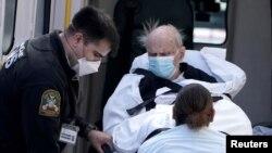 Pacijenta sa COVID-19 unose u kola hitne pomoći na Menhetnu, 27. marta 2020.