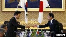 Ngoại trưởng Hàn Quốc Yun Byung-se (trái ) bắt tay Bộ trưởng Ngoại giao Nhật Bản Fumio Kishida tại Tokyo, ngày 21/6/2015.