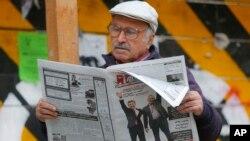 Seorang pria tengah membaca surat kabar lokal yang menampilkan PM Georgia Bidzina Ivanishvili dan presiden terpilih Giorgi Margvelashvili di halaman depan, di Tblisisi, Georgia (28/10).