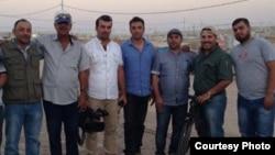 Slain Iraqi journalist Yasser Faysal al-Joumaili (holding a camera) pictured with Al Jazeera journalist Imran Khan (right) in Domiz refugee camp in Northern Iraq in September 2013. (Imran Khan/Al Jazeera English)