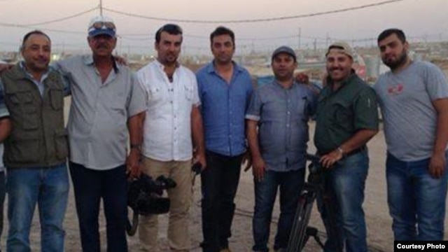 Slain Iraqi journalist  Yasser Faysal al-Joumaili (holding a camera) pictured with Al Jazeera journalist Imran Khan (right) in Domiz refugee camp in Northern Iraq in September 2013.  (Imran Khan/Al Jazeera English)