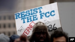 "A protester holds a sign that reads ""Resist the FCC. Text: INTERNET To: 52886"" at the Federal Communications Commission (FCC), in Washington, Dec. 14, 2017."