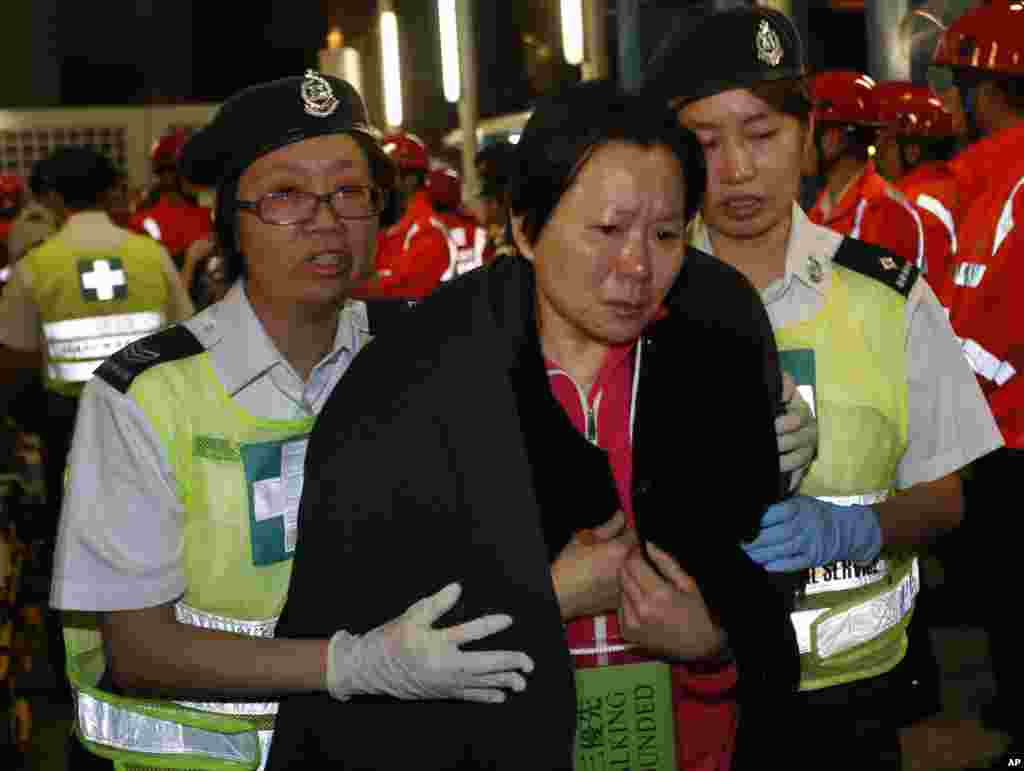 A survivor supported by rescuers, is taken onto shore after a collision involving two vessels in Hong Kong, October 2, 2012.