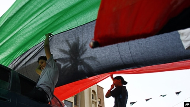 Libyan residents of Jamal Goubtan district in Tripoli hold a giant former Libyan flag for the cars driving under in the streets of Tripoli, Libya, Sept. 1, 2011