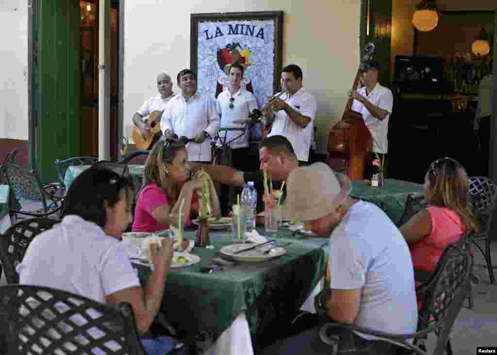 """Para musisi tampil menghibur turis di restoran """"La Mina"""" di Old Havana, Kuba (18/12).(Reuters/Enrique De La Osa)"""