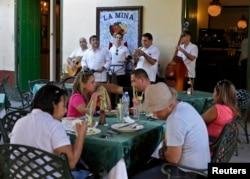 "Musicians perform as tourists dine at ""La Mina"" state restaurant in Old Havana, Cuba, Dec 18, 2014."
