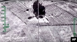 In this photo made from video footage provided by the Russian Defense Ministry on Dec. 9, 2015, a target is hit during an airstrike. Russia has unleashed another barrage of airstrikes against targets in Syria, including the first combat launch of a new cruise missile from a Russian submarine in the Mediterranean Sea.