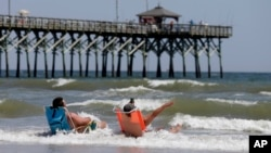 FILE - Vacationers sit in chairs along the surf in Oak Island, North Carolina, where two youths were hurt in shark attacks on June 14, 2015.