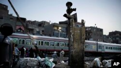 Orang-orang menunggu kereta melintas di Shubra, Kairo, 23 Oktober 2018 (Foto: AP Photo/Nariman El-Mofty)