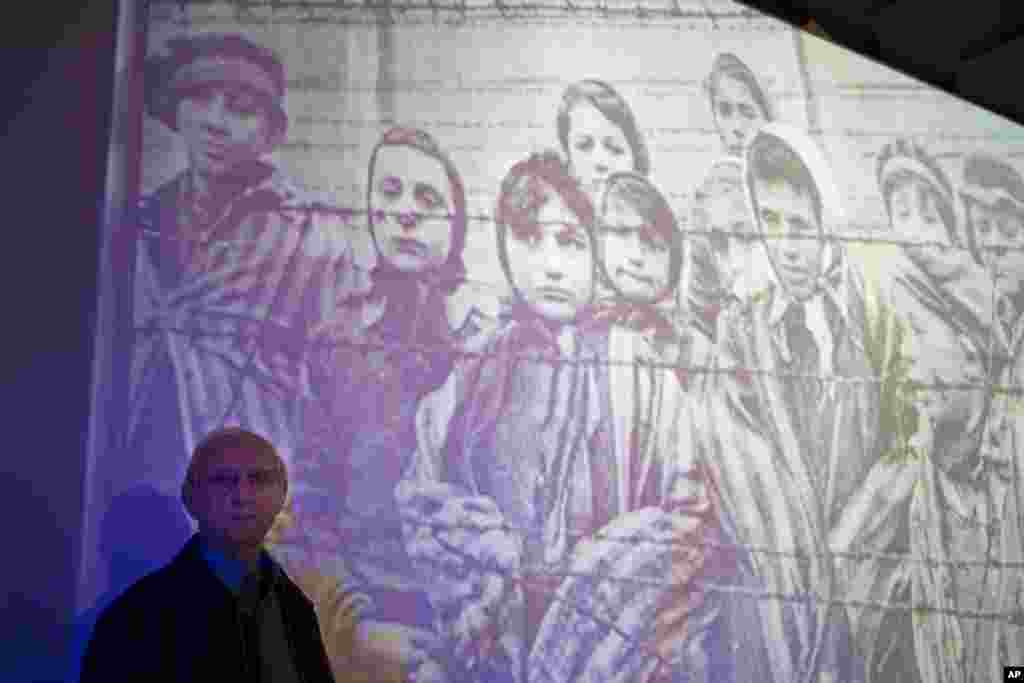 Auschwitz-Birkenau Holocaust survivor Tomy Shacham pose next to a photograph that shows him, on the left, on Jan. 27, 1945, during the International Holocaust Remembrance day ceremony in the Massuah international institute for holocaust studies in Kibbutz.