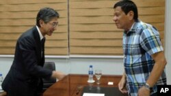 President-elect Rodrigo Duterte, right, receives Ambassador Kazuhide Isihikawa of Japan during a visit at Davao city hall, May 16, 2016. Duterte said Monday he would reimpose the death penalty, and target corruption after winning last week's election based on an unofficial count. (Office of the City Mayor Davao City via AP)