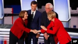 Sen. Amy Klobuchar, D-Minn., from left, South Bend Mayor Pete Buttigieg, Sen. Bernie Sanders, I-Vt., and Sen. Elizabeth Warren, D-Mass., greet each other before the first of two Democratic presidential primary debates hosted by CNN Tuesday, July 30, 2019.