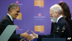 President Barack Obama and comedian David Letterman shake hands as they participate in a comedy show presented by the United Service Organizations (USO) and the military at Andrews Air Force Base, May 5, 2016. The event marked the USO's 75th anniversary.