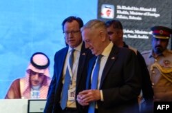 US Defense Secretary James Mattis (C) walks by as Saudi Arabia's Foreign Minister Adel al-Jubeir (L) is seen on a screen addressing the 14th International Institute for Strategic Studies (IISS) Manama Dialogue in the Bahraini capital, Oct. 27, 2018.