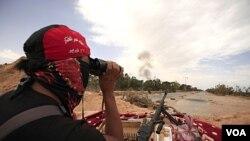 Anggota pasukan pemberontak Libya menggunakan teropong untuk mengamati suasana di kota Misrata.