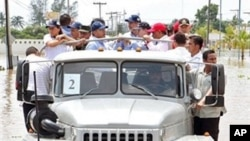 Handout photo released by Mexican Presidency of Mexican President Felipe Calderon (C-L) as he visits the area affected by Hurricane Karl in Veracruz, Mexico on 20 Sept 2010.