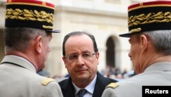 France's President Francois Hollande (C) speaks to military officials as he attends a ceremony to the memory of Stephane Hessel, at the Invalides in Paris, March 7, 2013.