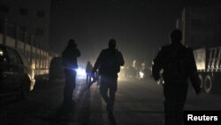 一名反政府武装人员(中)携带武器,与此同时,根据当地停火协议离开霍尔姆斯地区的民众和反政府武装搭乘巴士抵达叙利亚的伊德利卜市。