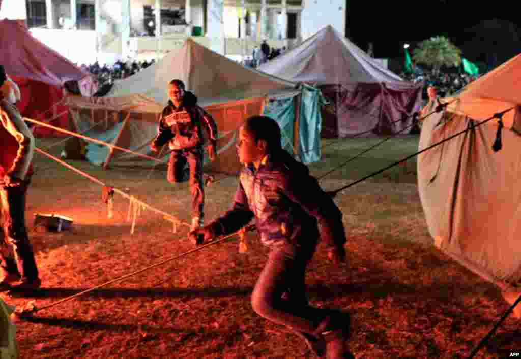 March 31: Libyans loyal Muammar Gaddafi run after journalists as they pass tents set up in Bab Al-Aziziyah, Gaddafi's heavily fortified compound in Tripoli. (Reuters/Zohra Bensemra)
