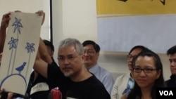 香港政治漫畫家尊子(左)展示一幅為和平佔中運動繪畫的漫畫,寓意香港的民主開花結果