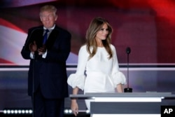 Melania Trump, wife of Republican Presidential Candidate Donald Trump walks to the stage as Donald Trump applaudss during the opening day of the Republican National Convention in Cleveland, July 18, 2016.