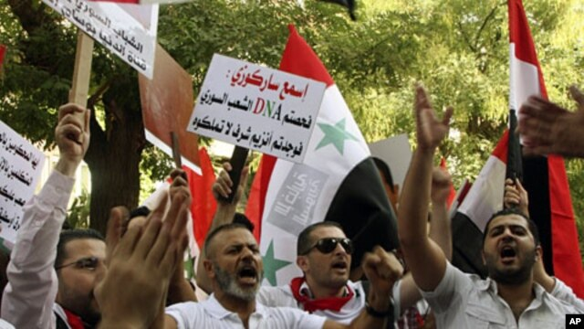 """Pro-Syrian regime protesters, shout slogans and hold up an Arabic placard read:""""Listen Sarkozy you checked the Syrian people's DNA and you found cells of honor that you don't have,"""" as they protest in front the EU mission office, in Damascus, Sept. 29, 20"""