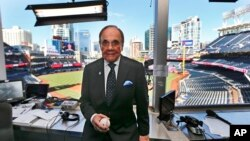 FILE - In this Sept. 29, 2016, file photo, Dick Enberg, the voice of the San Diego Padres, poses in his booth prior to the Padres' final home baseball game of the season in San Diego.