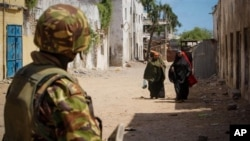 A soldier of the Kenyan Contingent serving with the African Union Mission in Somalia (AMISOM) stand guard on a street in the centre of the southern Somali port city of Kismayo. The mandate for AMISOM was recently extended.