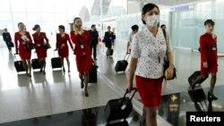 香港國泰航空公司的空姐在2003年中國非典疫情期間戴口罩上班。(2003年5月15日)