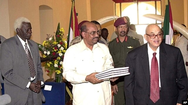 Sudanese President Omar Al Bashir, centre, holds the draft interim constitution for Sudan, in Khartoum, June 26, 2005, with the President of the Constitutional Court Judge Galal Ali Lutfi, right, and the Chairperson from Southern Sudan Abel Alair, left. (