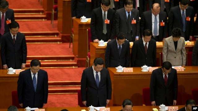 China's top leaders including Chinese President Xi Jinping, bottom center and Chinese Premier Li Keqiang, bottom right, have a moment of silence to commemorate the victims of a slashing spree during the opening session of the Chinese People's Political Consultative Conference in Beijing's Great Hall of the People, China, March 3, 2014.