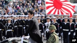 FILE - Japanese Prime Minister Shinzo Abe, center standing, reviews members of Japan Self-Defense Forces (SDF) during the Self-Defense Forces Day at Asaka Base, north of Tokyo, Oct. 23, 2016. Japan is debating whether to develop limited pre-emptive strike capability and buy cruise missiles.