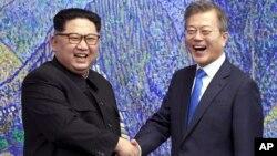 Lãnh tụ Triều Tiên Kim Jong Un (trái) bắt tay Tổng thống Hàn Quốc Moon Jae-in cho báo giới chụp hình bên trong Nhà Hòa bình tại làng đình chiến Panmunjom trong Khu Phi quân sự, ngày 27 tháng 4, 2018.